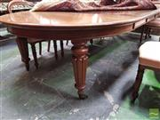 Sale 8485 - Lot 1052 - Early 19th Century Mahogany Round Extension Dining Table, with four later leaves, on turned reeded legs with brass castors