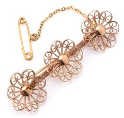 Sale 9132 - Lot 433 - A 9CT GOLD FILIGREE FLOWER BROOCH; 3 x 16mm flowers on bar setting marked De Beriche?, length 53mm with safety chain, wt. 3.74g.