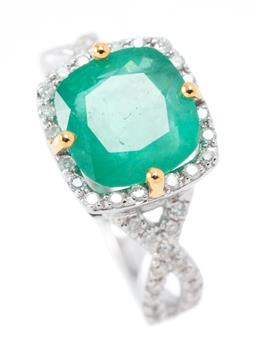 Sale 9169 - Lot 394 - AN 18CT WHITE GOLD EMERALD AND DIAMOND RING;  claw set with a cushion cut emerald of 3.20ct to surround and cross over shoulders set...