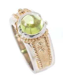Sale 9213 - Lot 360 - A SILVER GILT STONE SET RING; 11mm wide ring with decorative gilt top rub set with a round cabochon peridot, size L, wt. 7.82g.