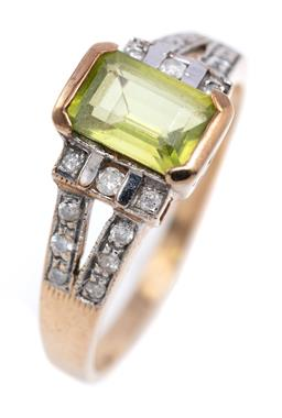 Sale 9194 - Lot 555 - A DECO STYLE PERIDOT AND DIAMOND RING; set in 10ct gold with an emerald cut peridot to split shoulders set with 18 Old European and...