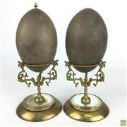 Sale 8649R - Lot 49 - Australiana Emu Eggs on Ornate Brass Display Stands with Mirrored Bottoms (finial missing on one) (H: 24cm)