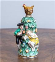 Sale 8650A - Lot 36 - A Chelsea style porcelain toy perfume bottle with figures around a tree and hen stopper, Height 9.5cm.