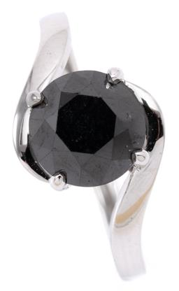 Sale 9164J - Lot 423 - A SOLITAIRE BLACK DIAMOND RING; four claw set in 9ct white gold with a round brilliant cut treated black diamond of approx. 2.60ct i...