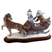 Sale 8000 - Lot 63 - A Lladro figural group of two children in a sleigh pulled by a dog, printed and impressed marks to base.