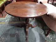 Sale 8792 - Lot 1054 - A Georgian oak wine table, with tilt top and turned pedestal on three outswept legs, H 69 x 77cm in diameter