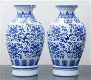 Sale 8562A - Lot 138 - A pair of Chinese white and blue vases, in bottle form, with exterior floral decoration and everted rims, H 36cm