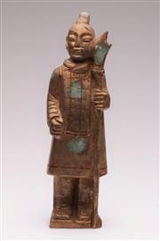 Sale 9049 - Lot 10 - Chinese green and gilt composite figure of a Han style warrior standing upright holding a weapon (H34cm)