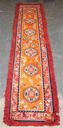 Sale 9121 - Lot 1034 - Nepalese wool runner with medallions & buddhist motifs in orange & red tones (255 x 85cm)