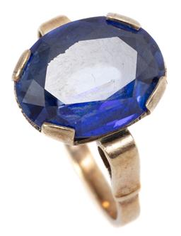 Sale 9145 - Lot 302 - A 9CT GOLD STONE SET RING; centring a 14 x 11mm oval cut synthetic blue sapphire with applied scroll shoulders size M, wt. 4.67g.