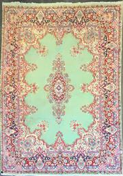 Sale 8792 - Lot 1072 - A mid C20th wool tabriz with central medallion and wide borders issuing flowers in red, cream and blue tones on a mint green floor,...
