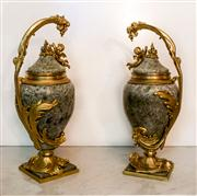 Sale 8516A - Lot 11 - A pair of impressive French lidded urns, marble & gilded bronze, featuring ornately detailed putti (cherubs) and intricate foliage m...