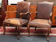 Sale 8942H - Lot 1 - A pair of French walnut armchairs fully upholstered in a distressed brown leather on cabriole legs, Height 105c x Width 56cm