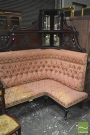 Sale 8345 - Lot 1078 - Late Victorian Mahogany Corner Conversation Seat, the carved top with mirrors & shelves, above a buttoned back & padded seat on cabr...
