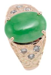Sale 9083 - Lot 467 - A 9CT GOLD JADE AND DIAMOND RING; featuring a 12.6 x 9mm cabochon green jadeite to scroll engraved shoulders set with 6 round brilli...
