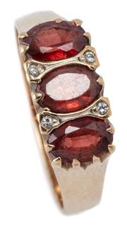 Sale 9046 - Lot 541 - A 9CT GOLD GARNET AND DIAMOND RING; 6.5mm wide ring set across the top with 3 oval brown garnets and 4 round brilliant cut diamonds,...