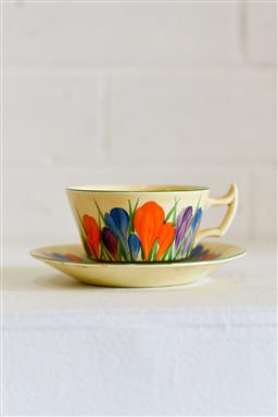 Sale 9153A - Lot 5024 - CLARICE CLIFF (1899 - 1972) - Bizarre Coffee Cup and Saucer in the Crocus Pattern c1930 cup: 9.0 cm height; saucer: 16.0 cm diameter