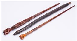 Sale 9185E - Lot 62 - A group of three carved timber staffs including fist form examples, longest Length 62cm