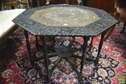 Sale 8359 - Lot 1021 - Indian or Sri Lankan Ebonised & Heavily Carved Table, the octagonal top with peacocks & pierced brass panel with fish & leaf motifs,...