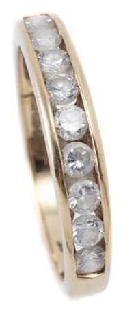 Sale 9046 - Lot 539 - A 9CT GOLD STONE SET RING; 3.7mm wide half hoop channel set with 9 brilliant cut zirconias, size P, wt. 2.19g.