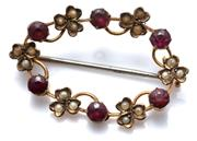 Sale 9037 - Lot 369 - AN EDWARDIAN 9CT GOLD GEMSET BROOCH; oval wreath set with round cut garnets and clovers set with seed pearls, size 32 x 20mm, wt, 2.2g.