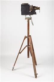 Sale 8765 - Lot 1069 - A vintage slide projector converted to a working lamp, mounted onto a large and sturdy timber tripod. Made by W.C Hughes Optician, B...
