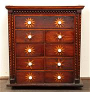 Sale 8871H - Lot 79 - An Australian cedar and pine naive cabinet of nine drawers with alternating starburst pattern and original porcelain handles, circa...