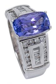 Sale 9054J - Lot 113 - A TANZANITE AND DIAMOND RING; bead claw set in 14ct white gold with a long chequerboard cushion cut tanzanite of 3.57ct above tapere...