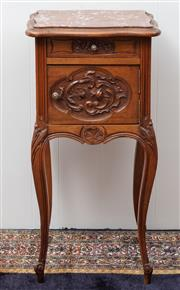 Sale 8940J - Lot 81 - An antique French walnut bedside cabinet or lamp table C: 1900. The serpentine shaped rouge marble top above a carved freize door on...