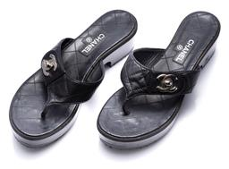 Sale 9186 - Lot 400 - A PAIR OF CHANEL BLACK LEATHER THONG SANDALS; quilted lambskin leather with silver tone crossed Cs to lacquered timber base, resole...