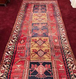 Sale 9190H - Lot 330 - A Persian rug with central rectangular motif on red ground, 333cm x 134cm