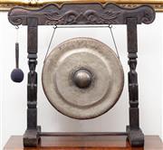 Sale 8940J - Lot 19 - A large antique Tibetan bronze circular gong in a carved frame accompanied by its padded striker. Ht: 77cm x W: 80cm x D: 32cm
