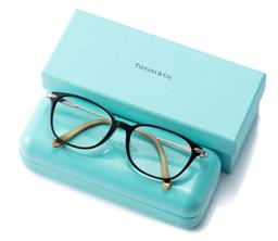 Sale 9186 - Lot 344 - A PAIR OF TIFFANY & CO GLASSES; black frames to metal arms, each arm set with a faux pearl and logo, no. TF 2096-H-F8001521714, in c...