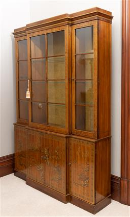 Sale 9260M - Lot 11 - A breakfront cabinet in the Chinoiserie style, the three glass doors revealing two layers of glass shelves over four cupboard doors...