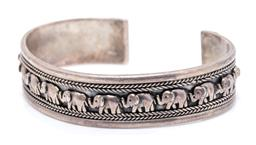 Sale 9246J - Lot 317 - A SILVER CUFF BANGLE; 15mm wide open bangle applied with a row of elephants between wire twist borders, diam 63mm, wt.33g.