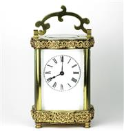 Sale 8402W - Lot 72 - A BRASS CARRIAGE CLOCK; of contoured customary form with applied scroll decoration, white dial with Roman numerals, bevelled glass o...