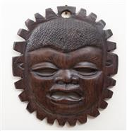 Sale 8868H - Lot 51 - An African tribal mask in the form of crying child and sun, diameter