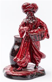 Sale 9083N - Lot 100 - A Royal Doulton flambe figure of the lamp seller. Height 23cm