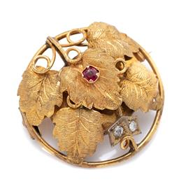 Sale 9099 - Lot 97 - An Australian Victorian round vine leaf brooch; set with two [2] old cut diamonds and a red stone in 18ct yellow gold; circa 1880.R...