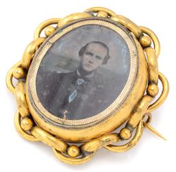 Sale 9140 - Lot 326 - AN ANTIQUE GOLD PLATED ROTATING LOCKET BROOCH; locket set with a portrait photo of a gentleman, reverse with a carved bone stag with...
