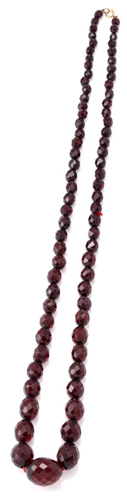 Sale 9140 - Lot 321 - A VINTAGE CHERRY AMBER COLOUR COMPOSITE BEAD NECKLACE; graduated 7-22mm faceted oval beads to bolt ring clasp, length 77cm, wt. 46.24g.